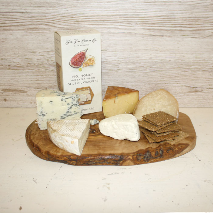 A wooden cheese platter on which rest five cheeses: Berkswell Ewe, Rosary Goat, Mrs Bell's Blue, Ribblesdale Smoked Goat, and Yorkshire Manchego. A pack of fig, honey, and extra virgin olive oil crackers rounds out the scene.
